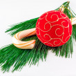 Royalty-Free Stock Photo: Christmas ornament and a candy can on pine twig on a white backg
