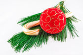 Christmas ornament and a candy can on pine twig on a white backg — Stock Photo