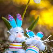 Stock Photo: Toy easter bunnies lounging in grass under white snowdrop