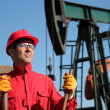 Stock Photo: Oil Industry Worker Holding Sledgehammer Next to Pump Jack.