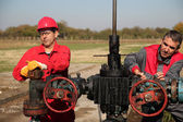 Two Skilled Oil and Gas Engineers in Action at Oil Well. — Stock Photo