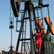 Stock Photo: Pumpjack and Oilfield Worker.