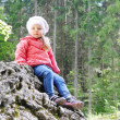 Little girl sitting on little mountain in green forest — Foto de Stock