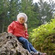 Stockfoto: Little girl sitting on little mountain in green forest