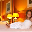 Little girl sitting on a bed — Stock Photo