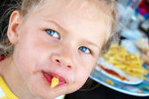Little girl soiled ketchup french fries — Stock Photo