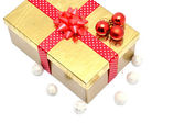 Golden gift box with red ribbon and red christmas balls — Stock Photo