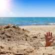 Stock Photo: Humans hand on sandy beach