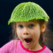 Little girl with leaf of savoy cabbage instead of a hat — Stock Photo
