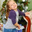 Little girl on background of christmas tree — Stock Photo