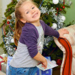 Little girl on background of christmas tree — Stockfoto