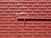 Red brick wall with water pipes — Stock Photo