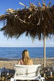 Mladá žena leží lehátko přímo u moře — Stock fotografie