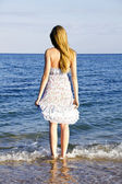 Young lady standing in the sea waves in the sunlight — Stock Photo