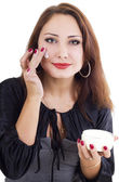 Smilling woman with face cream — Stock Photo