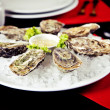 Raw oyster served with sauce — Stock Photo