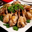 Fried quail with parsley on plate - Stock Photo