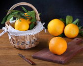 Oranges in basket and on cutting board with knife — Stock Photo