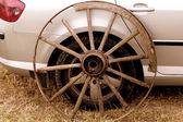 Old wagon wheel addition on new cars — Stock Photo