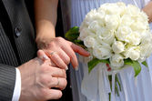Hands with wedding rings and bouquet — Stock Photo