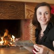 Woman near fireplace - Stock Photo