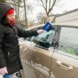 Woman cleans snow car windshield — ストック写真