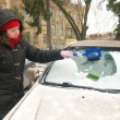 Woman cleans snow car windshield — Stok fotoğraf
