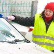 Woman cleans snow car windshield — Stock fotografie