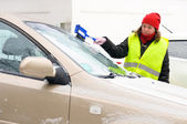 Woman cleans snow car windshield — Stock Photo
