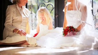 Elegant grandmother in wedding hat sitting with young bride cute flower girl