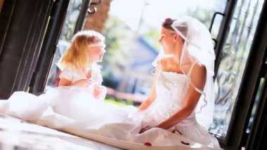 Portrait beautiful blonde girl wedding dress sitting floor cute little bridesmaid