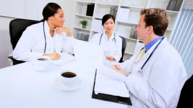 Young multi ethnic medical doctors meeting in the boardroom of a modern hospital building
