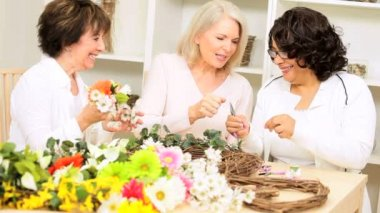 Multi ethnic older female friends crafting silk flowers