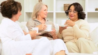 Group older multi ethnic ladies laughing drinking coffee home