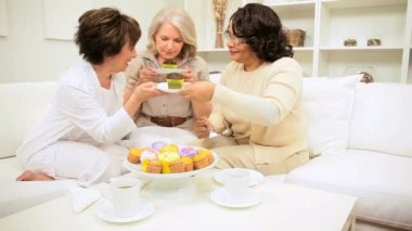 Multi ethnic older female friends enjoying coffee and cakes with gossip home