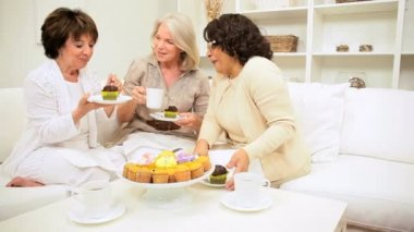 Three senior lady friends enjoying social afternoon with tea and cakes