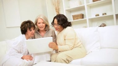 Three retired multi ethnic girlfriends home sofa enjoying online entertainment wireless laptop technology