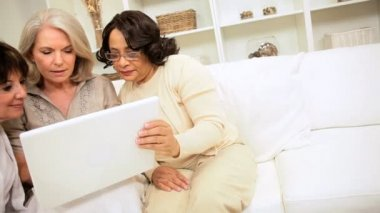 Group older multi ethnic ladies sitting home laughing at results seen wireless laptop