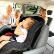 Parents Putting Children Family Car Seats - Foto Stock
