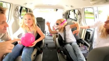 Little blonde girls playing with beach toys in family car while parents prepare for trip