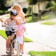 Vídeo Stock: CaucasiParents Child Encouraging Sister on Bicycle
