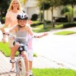 Young Parents Child Encouraging Sister on Bicycle — Stockvideo