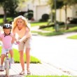 Cute Blonde Girl Practicing Bike Riding - Stockfoto