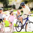 Young Caucasian Family Group Bicycles Outdoors - Stock Photo