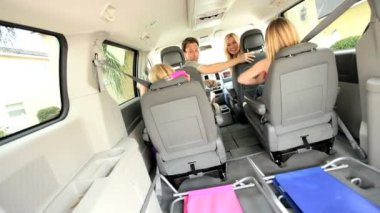 Happy blonde family in car preparing leave for beach vacation
