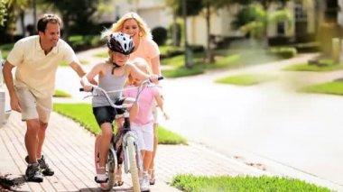 Caucasian parents and child encouraging older sister on bicycle