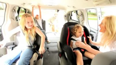 Young parents preparing children outing car strapping into seat belts