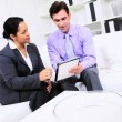 Business Executive Informal Working with Hispanic Assistant - Stock Photo