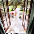 Brunette Bride on Balcony Wearing Wedding Dress - Stock Photo