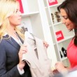 Blonde Boutique Manager Helping Fashion Conscious Client - Stock Photo